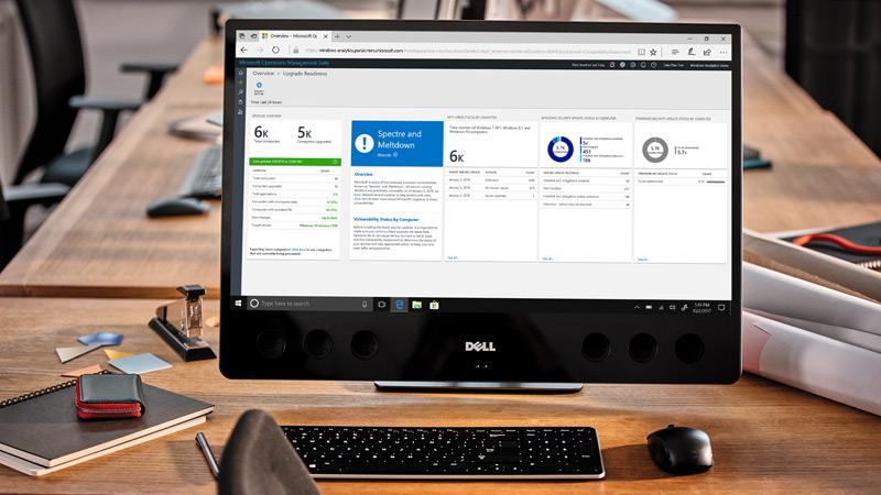 Desktop on table displaying Windows Analytics dashboard on screen