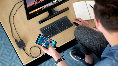 Man working with phone wired to the display