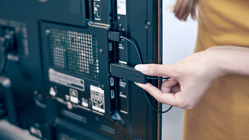Woman plugging in wireless adapter to display