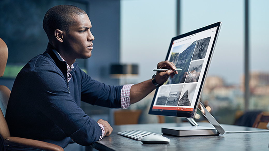 A man using Windows Ink and PowerPoint on a Surface Studio.