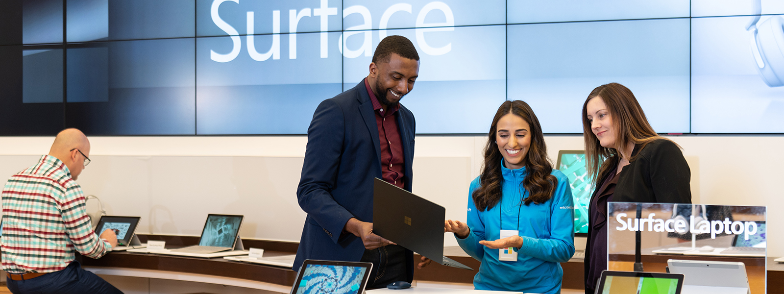 A female Microsoft Store employee looking at a laptop with a male and female customer.