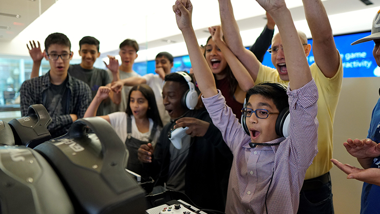 Halo players raising their hands at a Microsoft Store location.