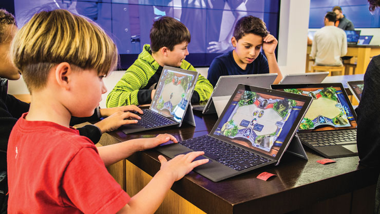 Children playing Hearthstone at a Microsoft Store location.