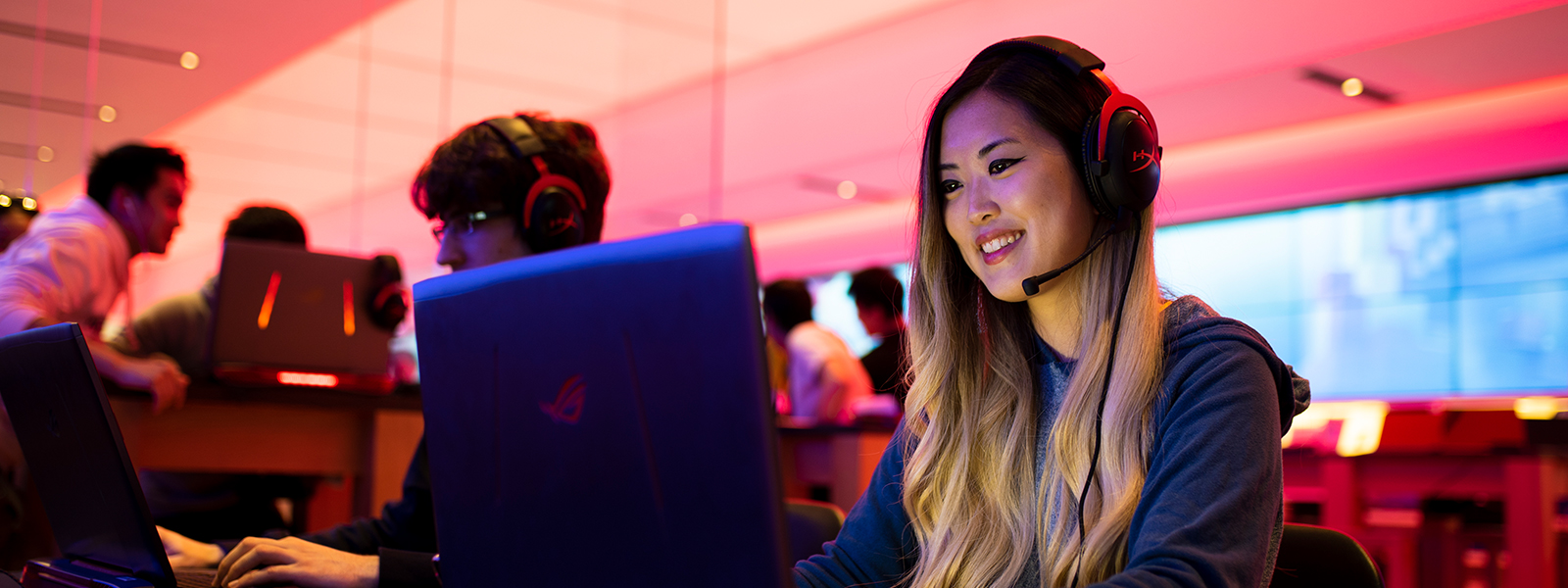 A female customer, with headphones on, gaming at a Microsoft Store location.