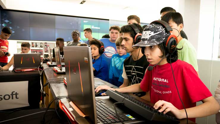 Group of young boys playing video games at Microsoft store.