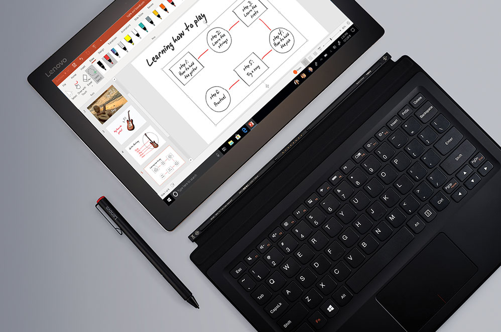 A Windows 10 2-in-1 in tablet mode showing a pen and detached keyboard with a PowerPoint presentation on screen