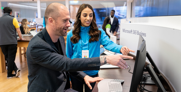 Female Microsoft employee helping a male customer while pointing and looking at a computer screen at a Microsoft Store location.