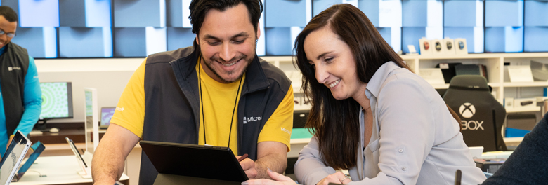 Male employee helping female customer with a Surface device at a Microsoft store.