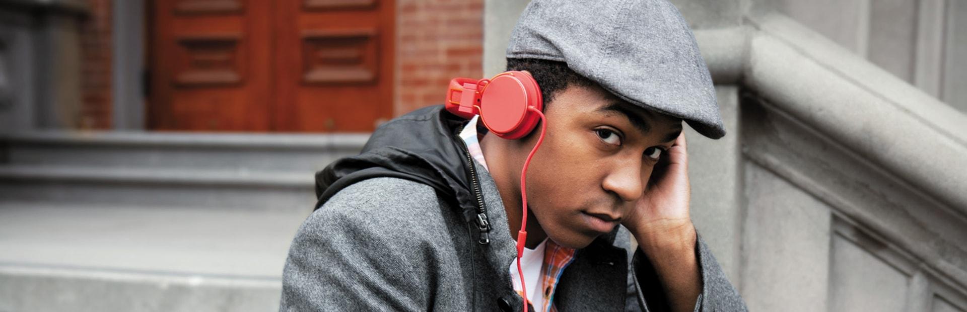 Man listening to Microsoft Groove music on red headphones