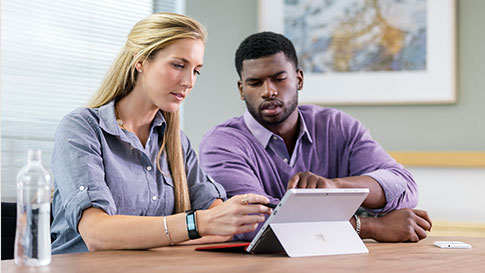 Woman and man in meeting room, reaching toward the display of a Surface Pro 4