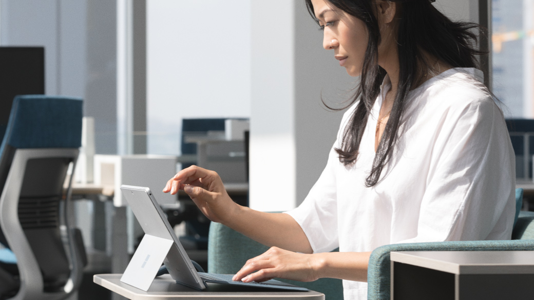 A woman uses Surface Pro in laptop mode at a desk.