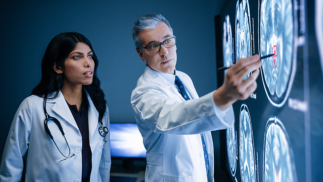 Two doctors point to Surface Hub as they look at Xrays.