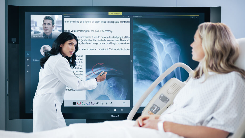 Doctor uses touchscreen on Surface Hub to show Xrays to patient sitting in bed.