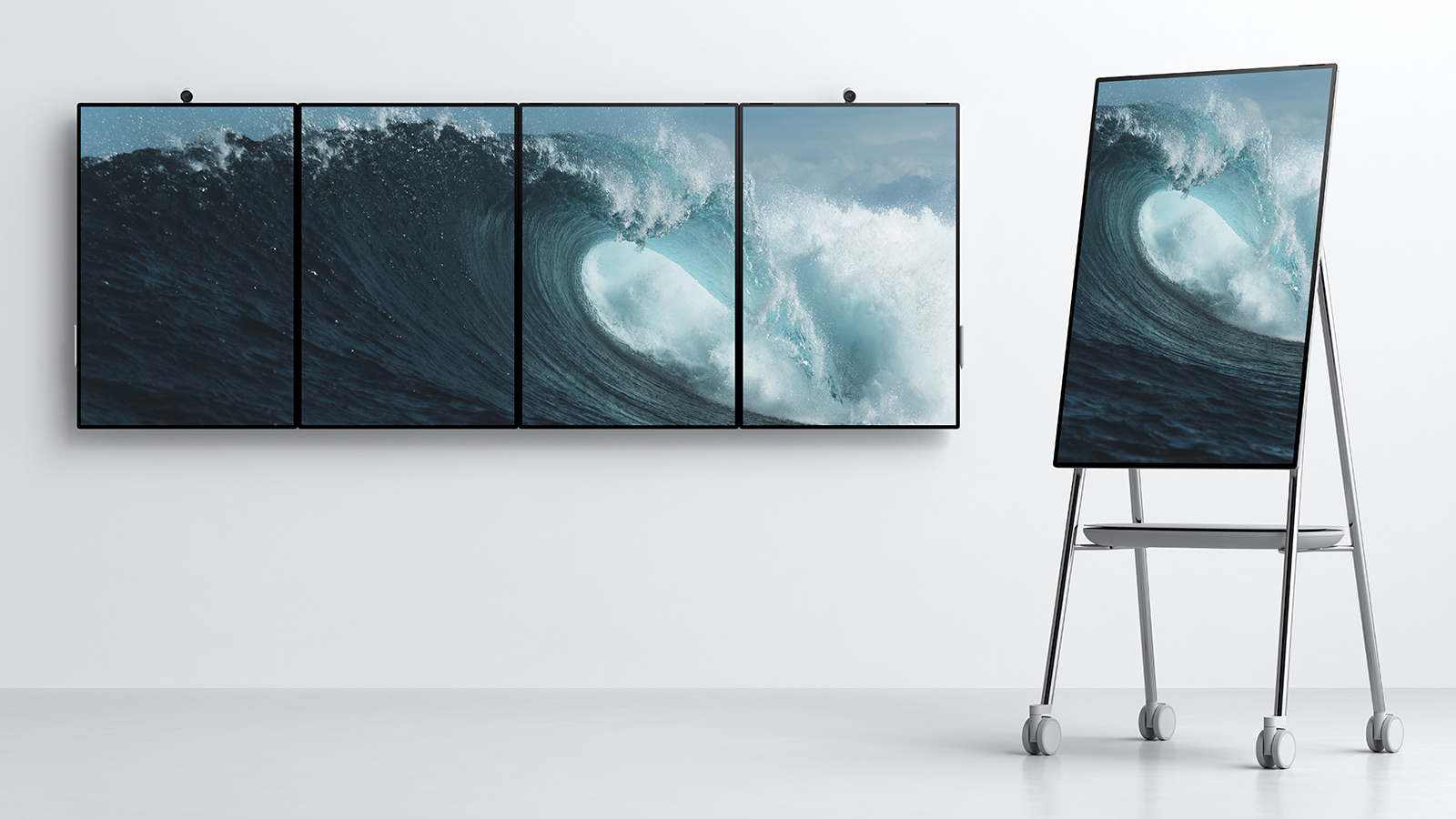 Four Surface Hub 2's tiled together on wall in portrait orientation, and one Surface Hub 2 rotated to a portrait orientation on a stand designed by Steelcase