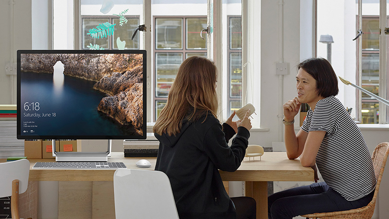 Two women talk at a conference table, with Surface Studio next to them.