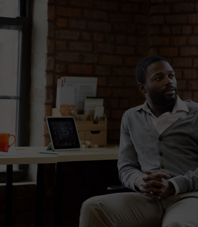 A man sitting by a desk with a tablet and a laptop, using Office 365 Business Premium.
