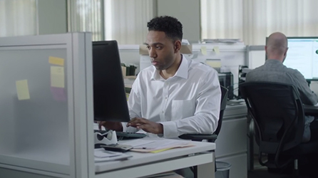 Workers sitting at desks in an office, start the in-page video How Point Solutions Block Productivity