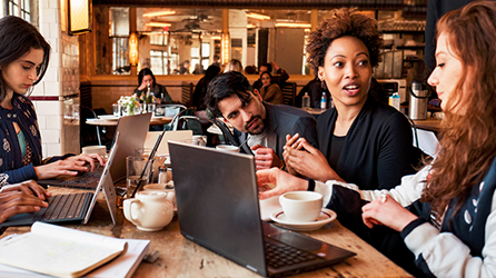5 people sitting at a table in a café, having a meeting. Download the guide, The Ultimate Guide to Chat-Based Tools, by completing the form on the destination page.