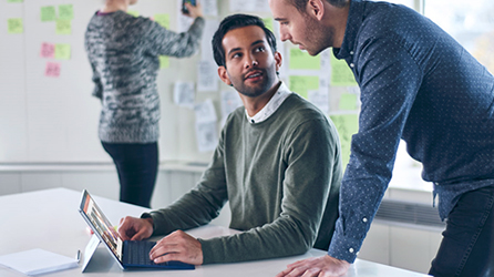 Two men working at a conference table and a woman looking at a whiteboard, download the eBook, Psychology of Workplace Collaboration, by completing the form on the destination page