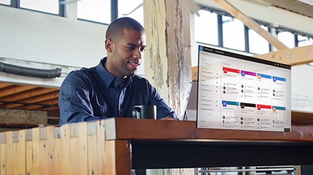 A man working at a desk, start the in-page video, SharePoint: The Future Starts Now