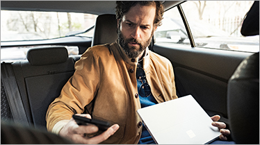 A man in a car with a laptop on his lap and looking at his phone