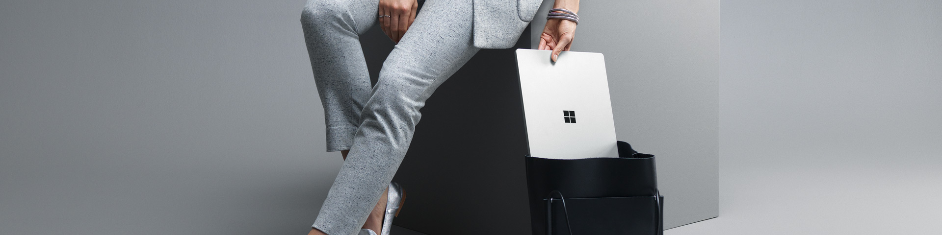 Woman sliding a Surface Laptop into her bag.