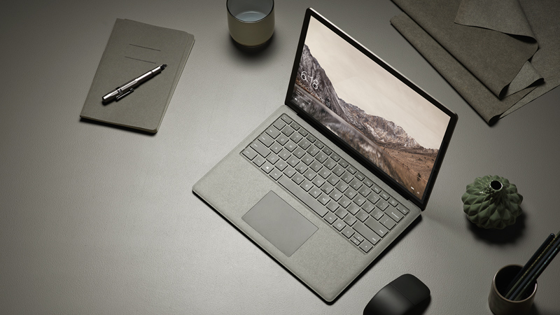 Birds eye view of Gold Surface Laptop with Black Arc Touch Mouse, on a desk in an office setting.