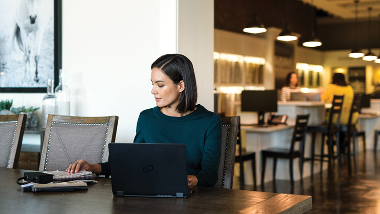 Woman sitting at a table with a laptop and notebook