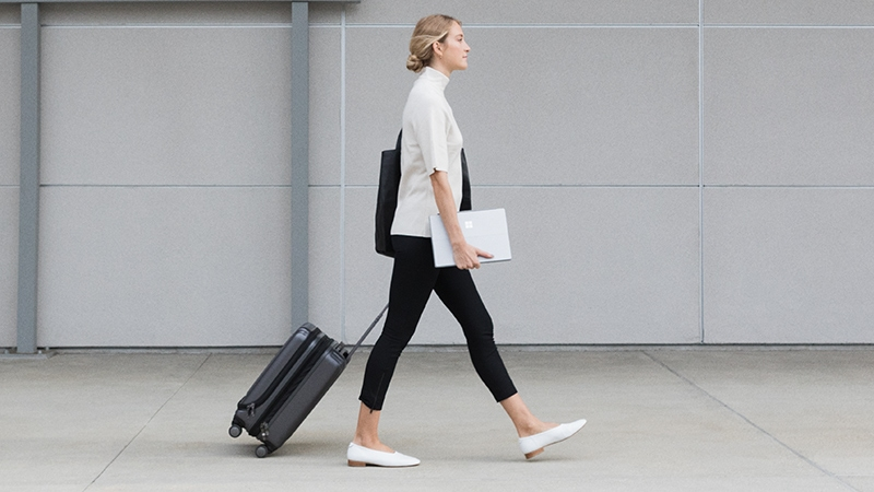 A woman holds a Surface Pro and rolls a suitcase.
