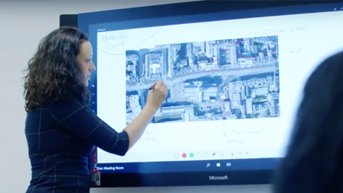 Woman uses Surface Pen on Surface Hub.