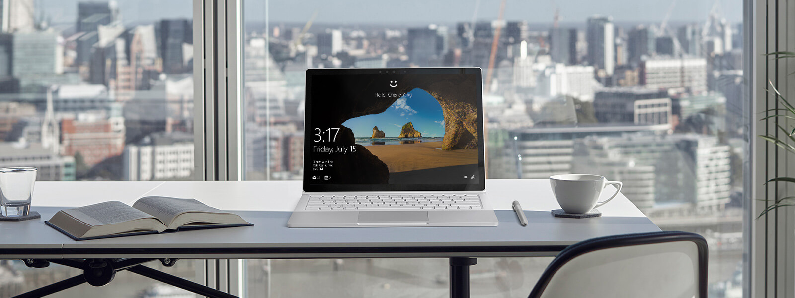 Surface Book with Hello screen on a desk, with city view in background.