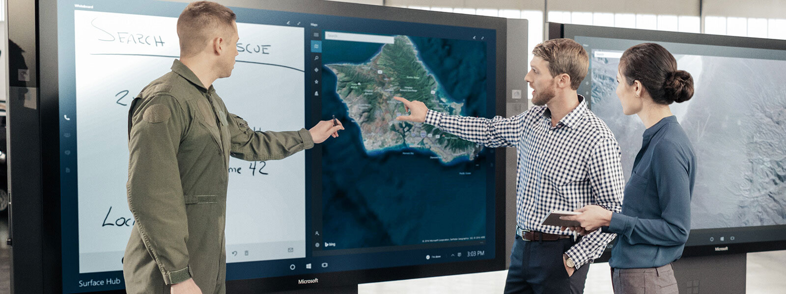 Woman and two men point to Surface Hub.