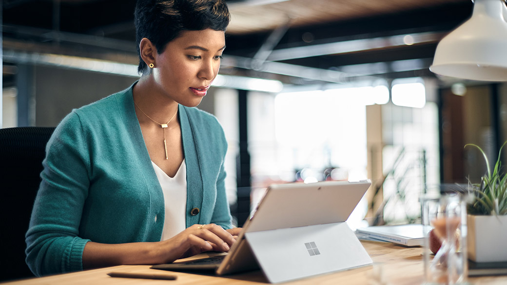 Woman types on Surface Pro 4 device at a table.