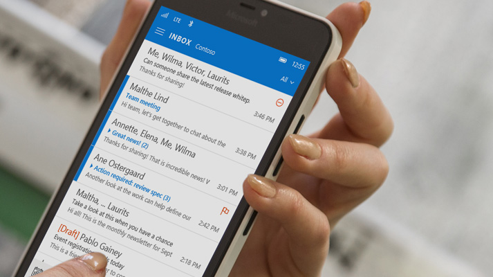 A hand tapping a message in an Office 365 email list on a smartphone.