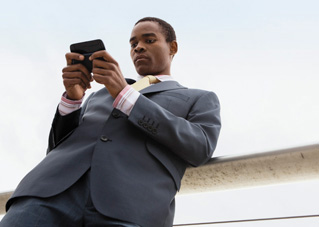 A man working on his phone outside, using Office Professional Plus 2013.