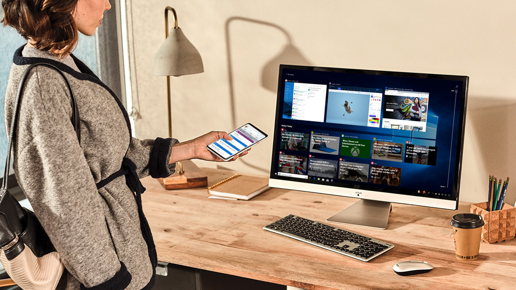 A woman holds her phone near her computer while using Timeline