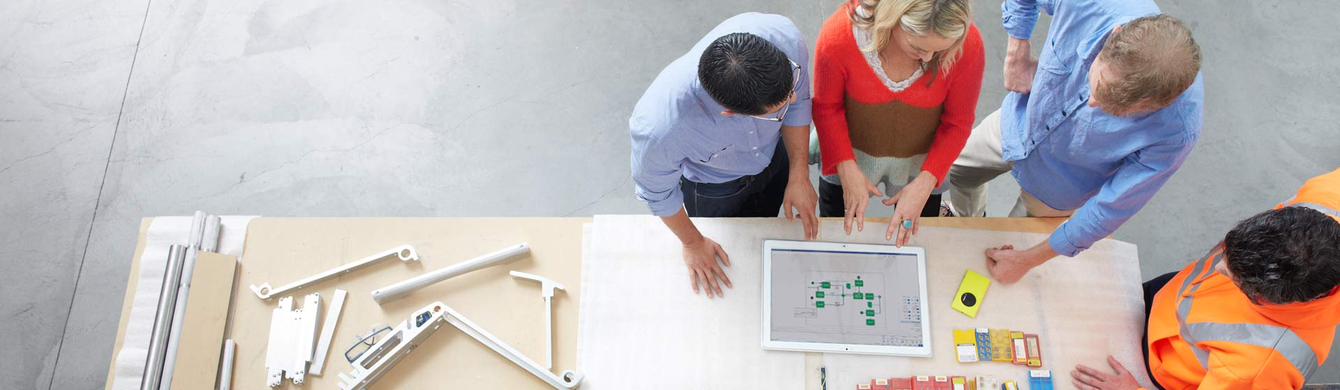 Four people standing at a table looking at a Visio diagram on a tablet computer image