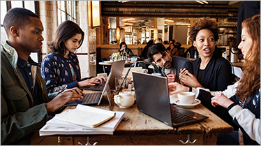 A group of people with laptops sitting and working together in a coffee shop