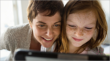 A woman and young girl smiling and looking at something on a computer
