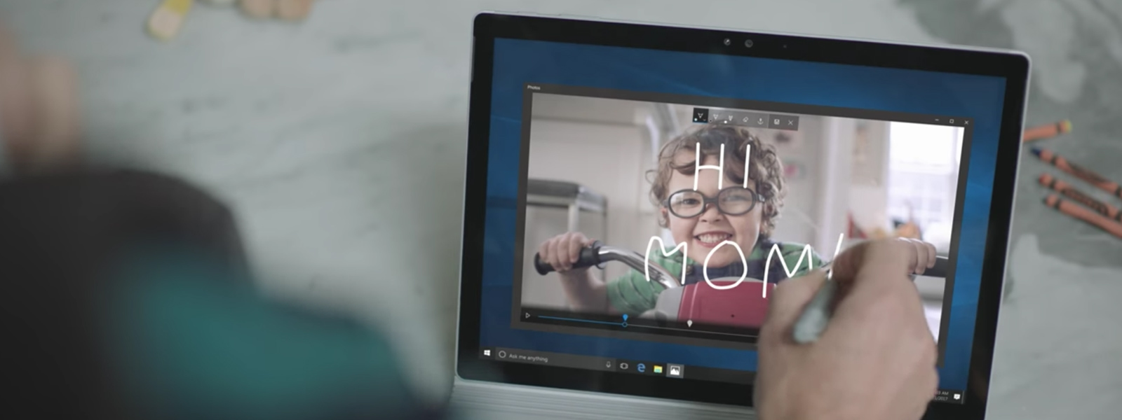 Woman on laptop, writing text over a movie of her young child. The words 'Hi Mom' appear over a speckled young boy on a tricycle