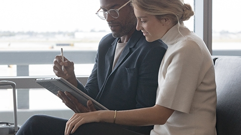 Man uses Surface Pen on a Surface Pro in tablet mode, and shows something to a woman who sits next to him in an airport.