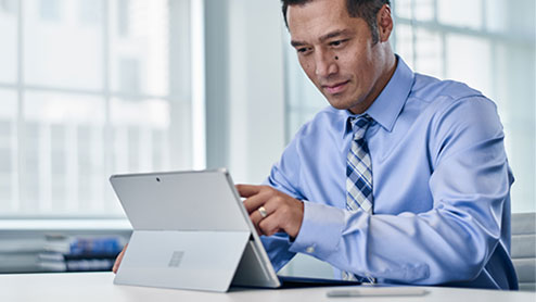 a well-dressed business man typing on his surface