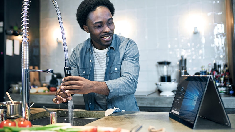 Man looking at Cortana on a 2-in-1 device displaying Cortana on the screen, while running water in the kitchen sink