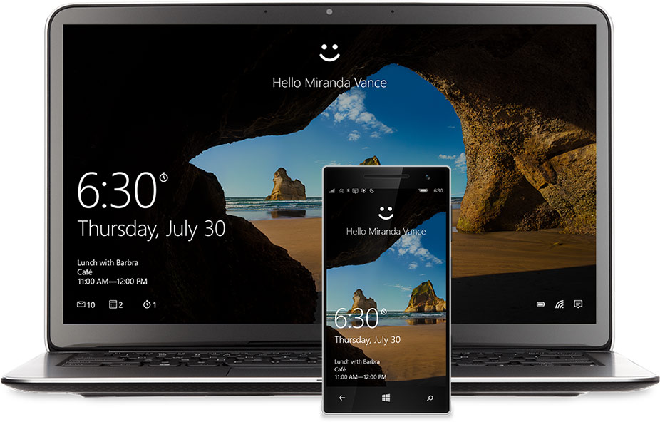 """A laptop and phone with the Windows 10 Start screen on the display. There's a smiley face at the top of each above the words, """"Hello Miranda Vance"""""""