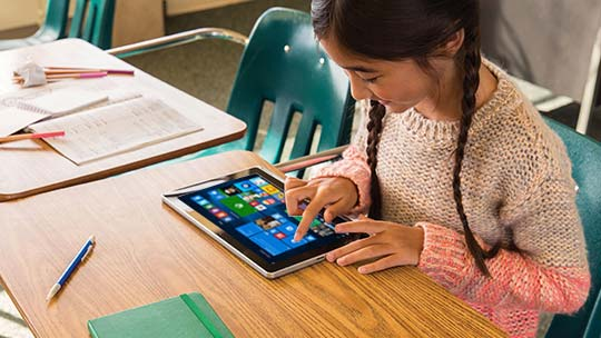 A girl using Windows tablet at school. Learn more about Microsoft Aspire Student Program.