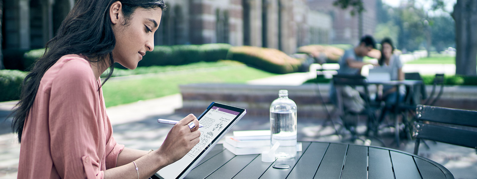 Woman sits in outdoor setting, using touchscreen of Surface Pro 4 in tablet mode.