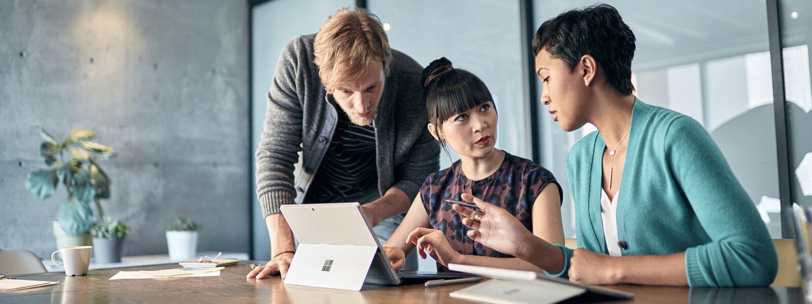 Three people are looking at a Surface Pro 4 in a conference room.