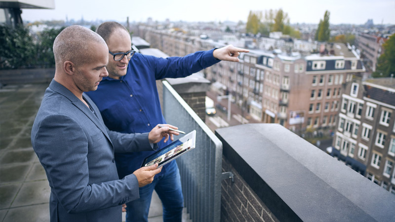 Two man outside on a rooftop working with a tablet