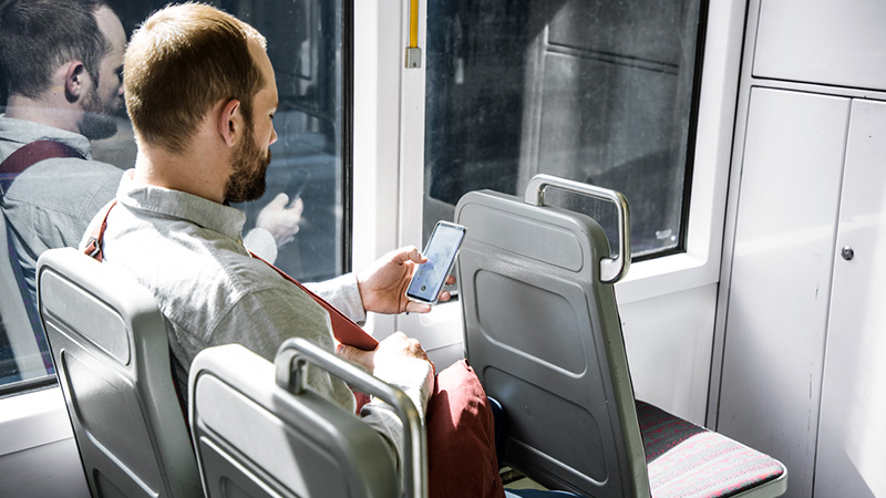 A man in a public transport looking at a mobile phone