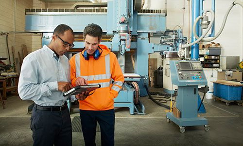 Two production employees working with surface